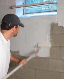 armorlock basement waterproofer in white being applied by man to wall